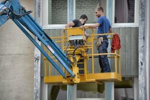 Deux ouvriers sur une nacelle de chantier