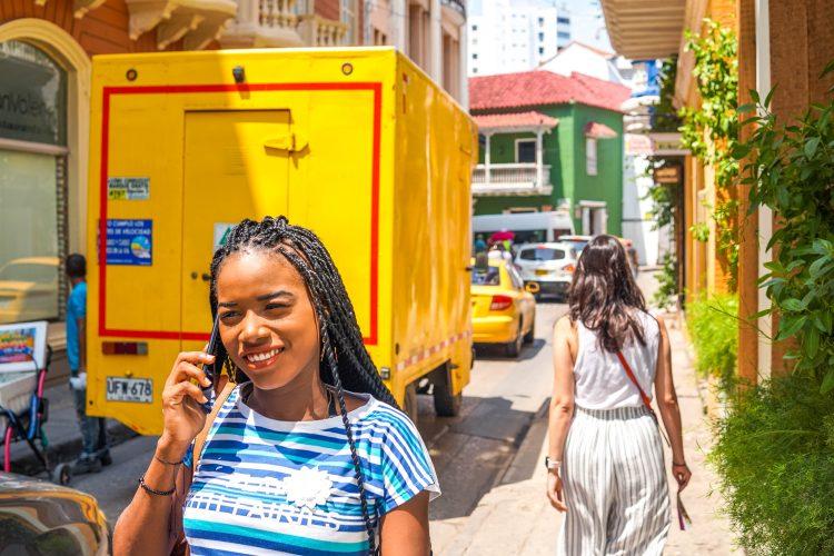 Jeune femme métisse qui marche dans la rue en téléphonant